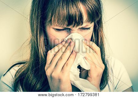 Woman With Allergy Or Flu Cold Symptoms Sneezing In Tissue
