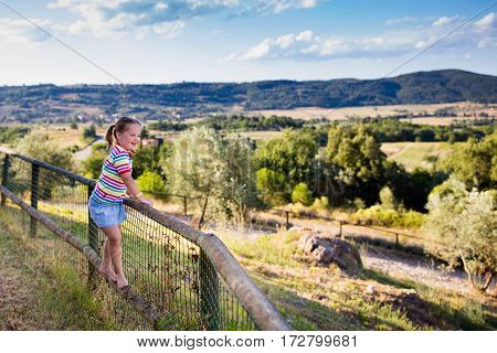 Happy little girl enjoying beautiful valley and mountains view of Tuscany landscape during summer vacation in Italy. Child playing on villa terrace during Italian holiday. Family traveling in Toscana