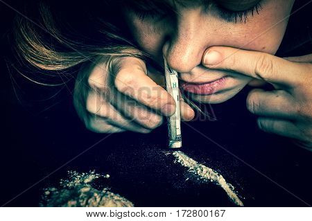 Junkie woman snorting cocaine powder with rolled banknote on black background - retro style