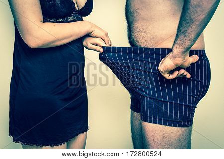 Man and woman looking down into underwear - impotence concept - retro style