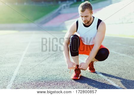 Man crouched in red sneakers for running. Man tightening lacings on his sneakers. Sportsman on stadium before running. Outdoors, sunlight, stadium