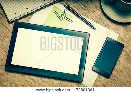 Digital tablet with blank screen and mobile phone on wooden table in business office - retro style