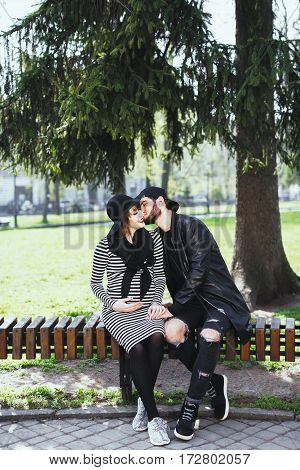 Man and pregnant girl sitting on bench in park. Young couple, love story, pregnant girl. Outdoors, full body