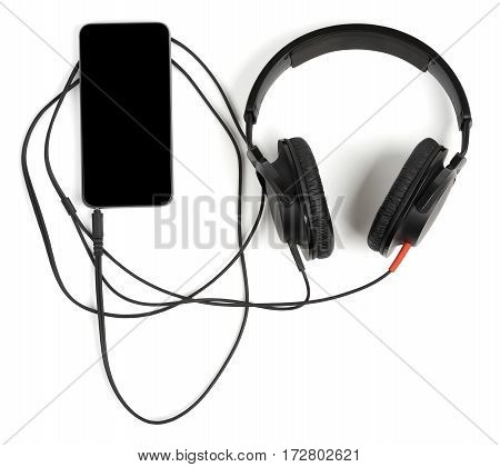 Closed back stereo headphones connected to smart phone for listening music or watching videos isolated on white background