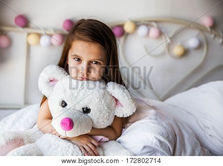 Little girl with her teddy sitting on the bed. home comfort family relationships people