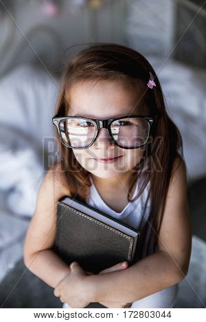 Preschooler girl with books and glasses. teaching student education