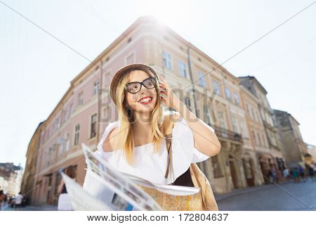 Happy tourist girl with light hair and red lips wearing hat and glasses, holding map at old European city background and smiling, portrait.