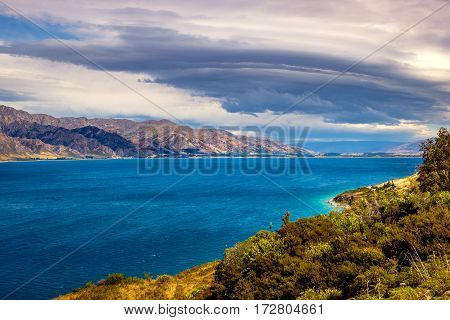 Landscape View Of Lake Hawea And Mountains With Dramatic Sky, Nz