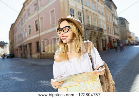 Beautiful tourist girl with light hair and red lips wearing hat and glasses, holding map at old European city background, portrait.