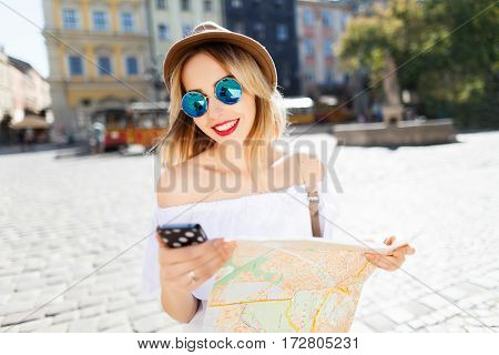 Stunning tourist girl with light hair and red lips wearing hat and glasses, holding map and mobile phone at old European city background and smiling, sunny weather.