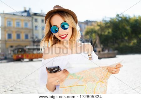 Gorgeous tourist girl with light hair and red lips wearing hat and glasses, holding map and mobile phone at old European city background and smiling.