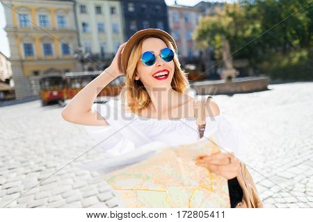 Pretty  tourist girl with light hair and red lips wearing hat and glasses, holding map at old European city background, sunny weather.