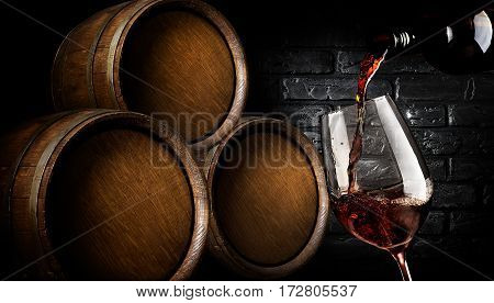 Wooden barrels and wine pouring into wineglass in cellar