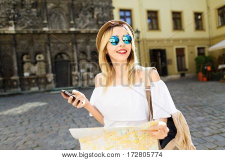 Beautiful tourist girl with light hair and red lips wearing hat and glasses, holding map at old European city background and smiling.