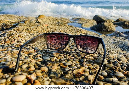 Black sunglasses lying on rocks near the sea, copy space, close up, summertime, colorful photo.