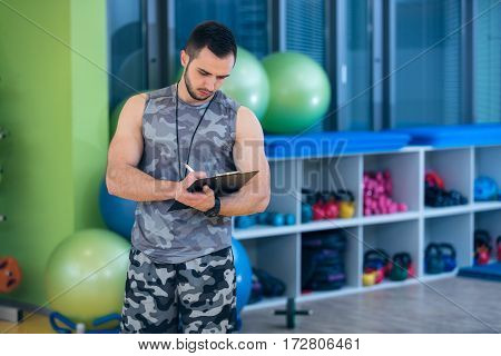 Portrait of a muscular trainer writing on clipboard.