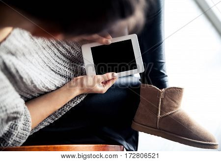 A girl holding a tablet in hands reader with a nice manicure. Leather trousers ugg boots. Fashion style learning modern recreation