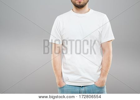 Man with beard in white T-shirt and jeans. Mockup. Hands in pockets. Portrait without head. Indoors, studio