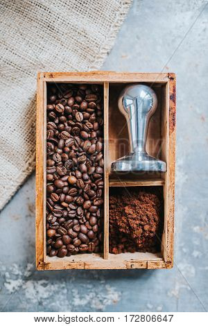 Freshly ground coffee coffee beans and tamper in vintage wooden box