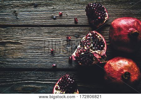 Fresh red pomegranate and grapefruit On a wooden background. Pomegranate in plate on wood background. Pomegranate on wood textured background. Overhead view image.