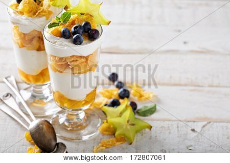 Yogurt cereal parfait with mango and tropical fruits, layered dessert or breakfast