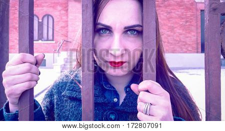 Sad woman behind bars staring intently into the eyes of camera with depressed facial expression hopeless - Concept of people mental heath and today social human problems