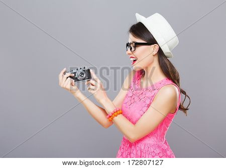 Lovely young girl with dark hair and red lips wearing pink dress and sunglasses posing with camera at gray studio background, portrait, copy space.