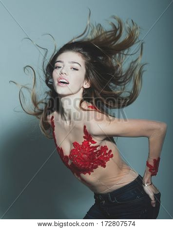 young pretty woman or cute sexy girl with long beautiful curly blonde hair on adorable face in red embroidered bodysuit and jeans on grey background