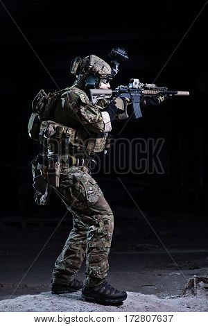 Soldier with rifle in helmet with night vision device aiming to target on dark background