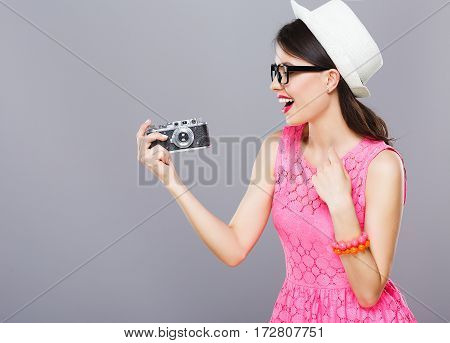 Smiling young girl with dark hair and red lips wearing pink dress and sunglasses posing with camera at gray studio background.