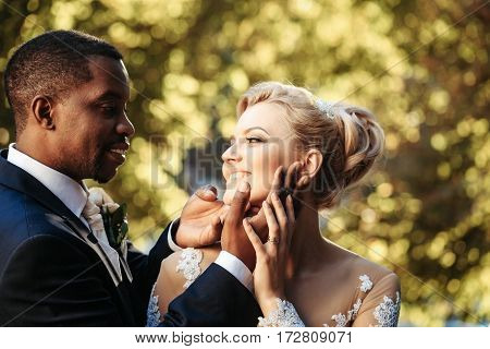 Loving Groom Touches Face Of Adorable Bride