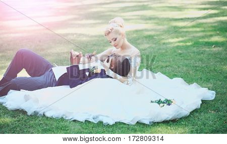 Man Lying In Arms Of Cute Bride On Green Grass