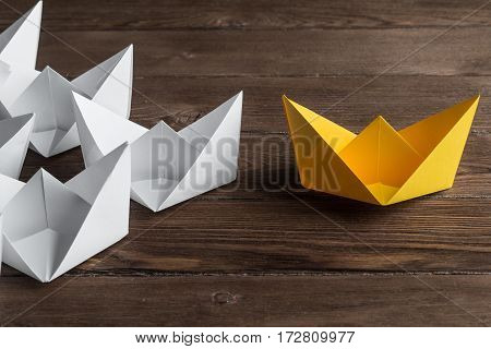 Set of origami boats on wooden table, one yelllow and the rest all white.