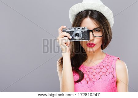 Attractive young girl with dark hair and red lips wearing pink dress and sunglasses posing with camera at gray studio background, portrait, copy space.