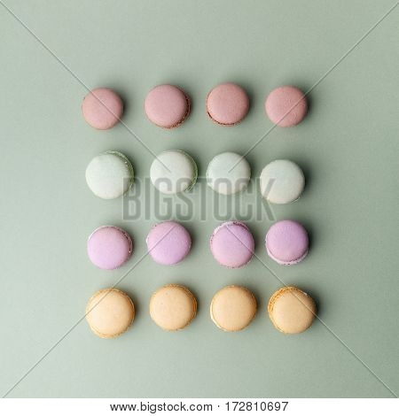 Sweet colorful macarons on green background. Top view