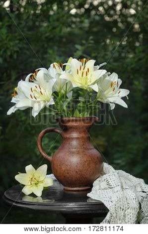 Bouquet of white lilies on the old table in the summer garden. Low key, selective focus, space for text.