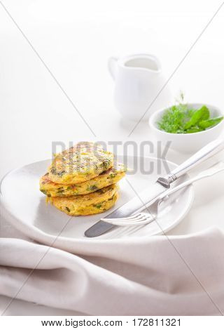 Healthy vegetarian zucchini fritters on a white surface