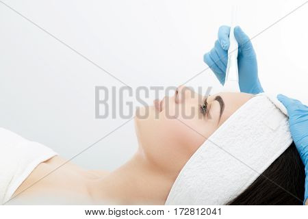 Model lying on couch. Brush touching her face. Cosmetological clinic. Healthcare, clinic, cosmetology