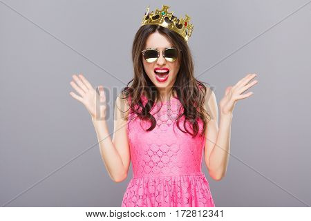 Angry young girl with dark hair and red lips wearing pink dress, sunglasses and crown posing at gray studio background, portrait.