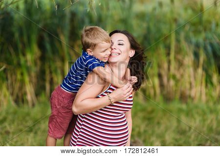 Boy kissing and hugging his pregnant mother. Happy mother and her son. Green background blurred, outdoors.