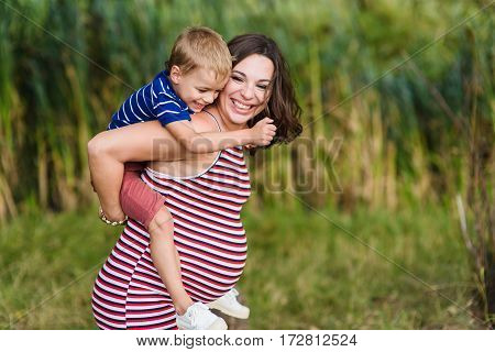 Child sitting on the shoulders of his pregnant mother. Happy mother and her son. Green background blurred, outdoors.
