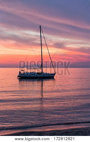 Sailboat sunset silhouette is a sailboat sailing along the water with a colorful purple and pink night sky in the background