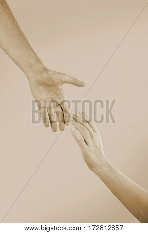 Male and female hands on light background, toned in sepia