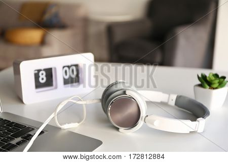 Headphones, clock and laptop on office table