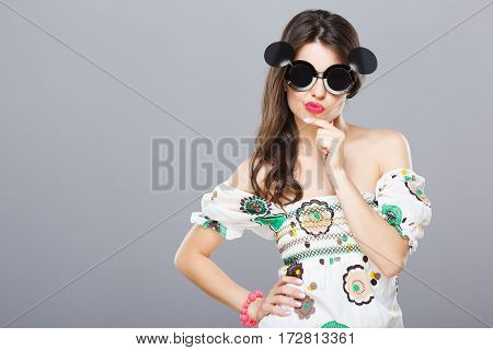 Beautiful girl in black round sunglasses with side glasses. Looking at camera, hand on waist, thoughtful. Summer outfit, floral dress. Waist up, studio, indoors