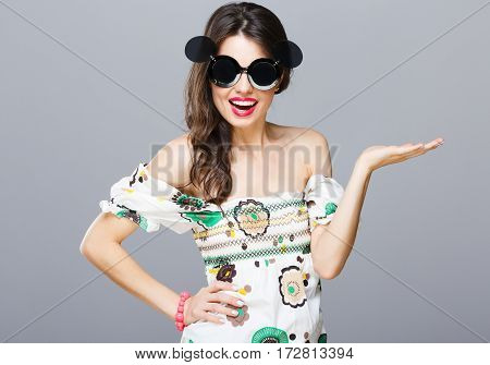 Beautiful girl in black round sunglasses with side glasses. Looking at camera, hand on waist, another hand aside. Summer outfit, floral dress. Waist up, studio, indoors