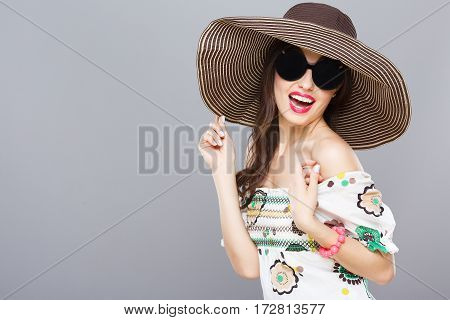 Beautiful girl in hat and black round sunglasses. Looking at camera, smiling widely. Touching hat. Summer outfit, floral dress. Waist up, studio, indoors