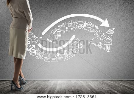 Back view of confident businesswoman in empty concrete room with sketches on wall
