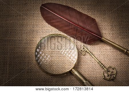 Old key near feather and magnifying glass on canvas background.