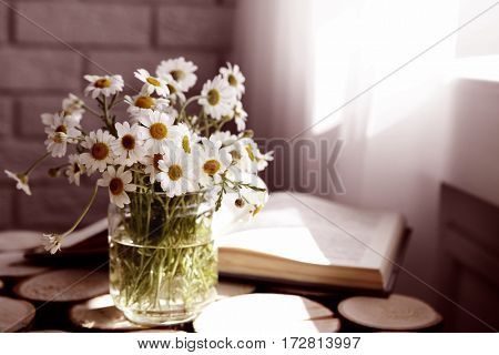 Chamomile bouquet in glass vase on wooden background